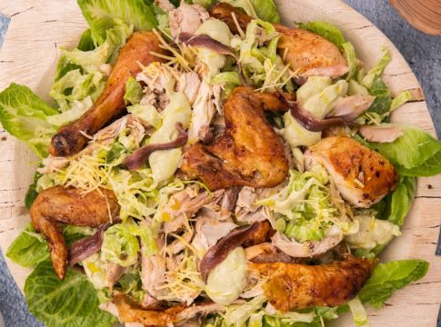 Cooked chicken pieces and grated cheese on bed of lettuce on a wooden tray with a pair of salad server on blue background