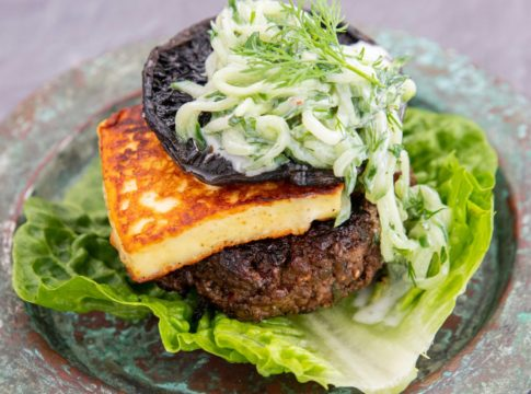 Burger , haloumi cheese,mushroom and white vege salad on a piece of lettuce on rustic plate