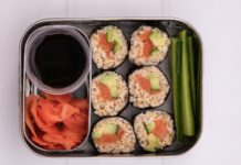 6 rolled sushi,cucumber sticks, small pot of soy sauce and pink ginger in a box on white board