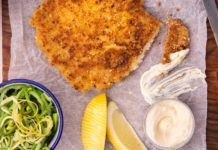 A piece of chicken schnitzel, a bowl of green salad, lemon wedges and a blob of mayonnaise and a knife on a wooden board