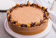 Coffee brown round cake decorated with walnuts and chocolate on white board on white fabric.