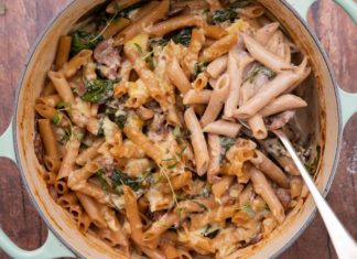 A pale blue 2 handle casserole filled with penne pasta with a silver spoon on wooden board