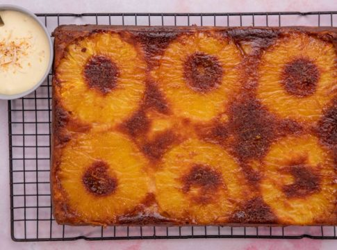 Large rectangle cake with 6 pinapple rings on wire rack with a small pot of cream