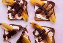 4 square toast topped with white cream, banana slice and drizzle of chocolate on pink background