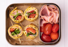 4 colourful rolled food with skewers, 4 mini tomatoes and some sliced ham in an oblong box on white board.