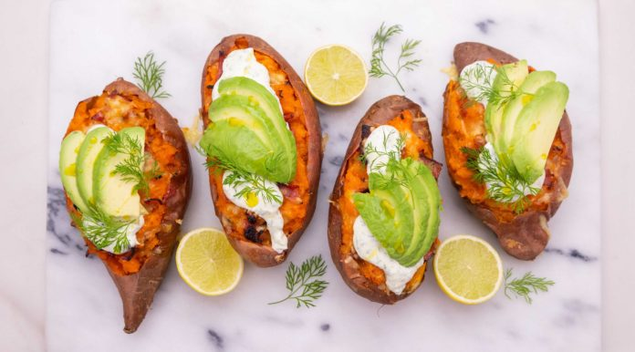 4 orange sweet potatoes topped with white cream and avocado slices, 3 lemon halves and bits of dill on white marble board.