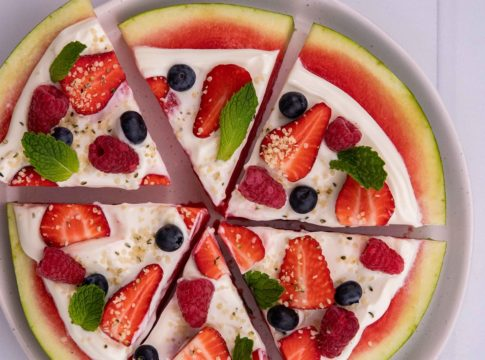 Round watermelon slice topped with white cream,berries and mint, cut into wedges on a round plate on white board