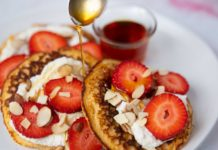 3 pancakes topped with white cream, strawberries and almond slices with a spoon pouring syrup and a small pot of it.