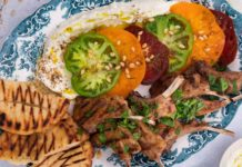 A platter with toasted pita bread, lamb cutlets, sliced green and red tomatoes on white sauce and nuts sprinkle.