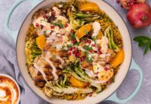 Light blue pan with handles filled with orange, green brown food and red berries scattered on top. A pot of yoghurt and pomegranate at sides.