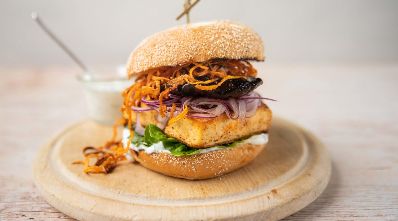 A burger with lettuce, square tofu, red onion, mushroom and fried carrot inside on a wooden round board and a small glass pot of white sauce at back. pot of