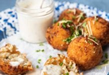 4 brown deep fried balls topped with herbs and one broke in 2 halves and a glass jar of white sauce on blue rimmed plate on blue grey background.