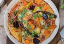 Top view of a round quiche with roasted vegetables in a pie dish, a knife and herb beside.