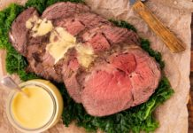 Roast beef slices on green on wooden board with yellow sauce and sauce pot.