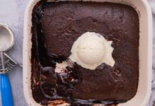 Top view of square chocolate sponge with a scoop of white ice cream in the middle with an ice cream scoop spoon at side.