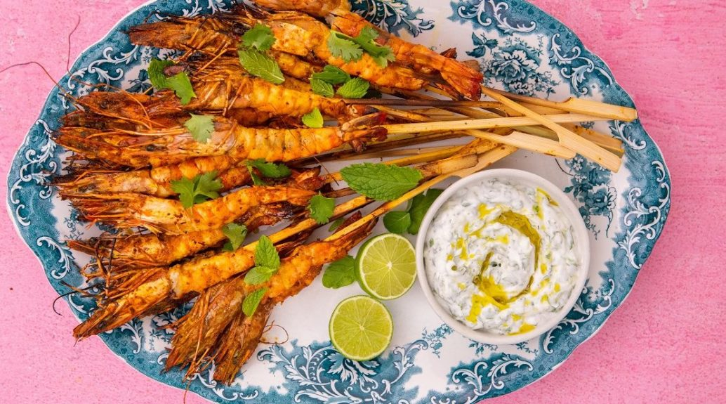 Cooked large prawn skewers on blue and white oval platter with lime halves and a pot of white sauce on pink background