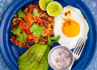 A fried egg, orange rice, avocado slices, lime halves a pot of red powder and a fork on blue round plate on light blue background