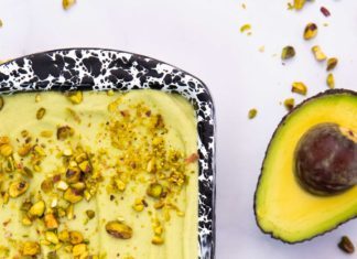 Part of black and white metal tin full of pale green cream topped with chopped nuts and an avocado half on white marble background, with chopped nuts scattered all over.