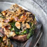 3 large mushrooms stuffed with greens and nuts on a metal plate with a knife and fork.