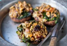 3 large mushrooms stuffed with rice,greens and nuts on a metal plate with knife and fork.