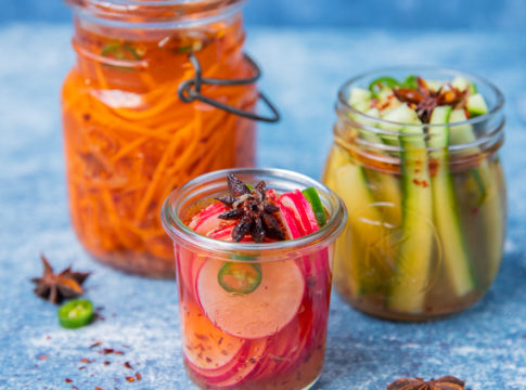 3 jars of pickled vegetables, carrot, cucumber and radish on blue paper