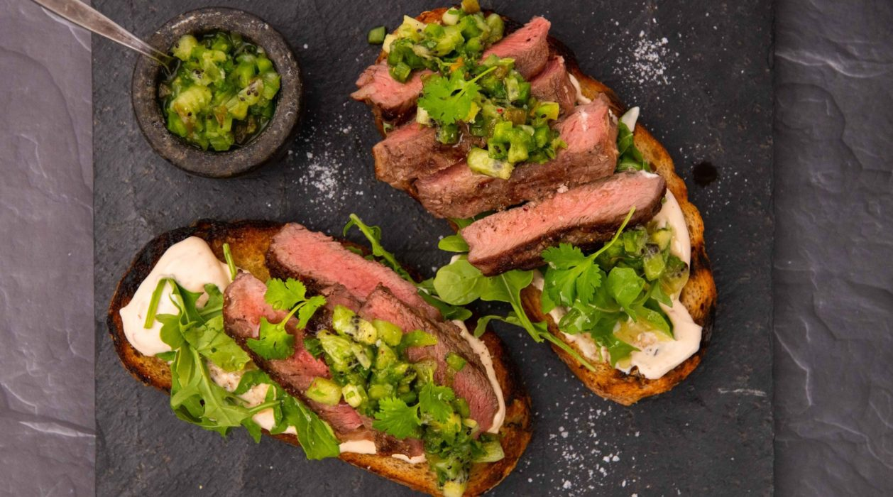 Two pieces of bread topped with cut steak, green salsa and white sauce under them on a stone slate with a small pot of green salsa.