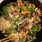 Beef, vegetables, cashews and noodles in a large two-handle orange dish with a pair of chopstick on white cloth.