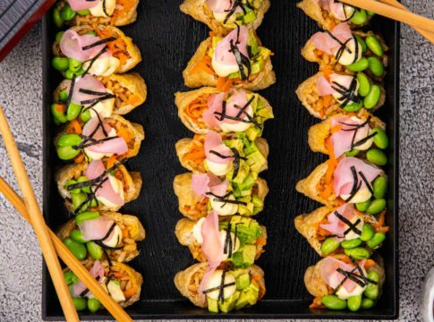 3 rows of 7 stuffed tofu pockets topped with pink and green food in black square box and two pairs of chopsticks, 3 small pots of pink, black and green food