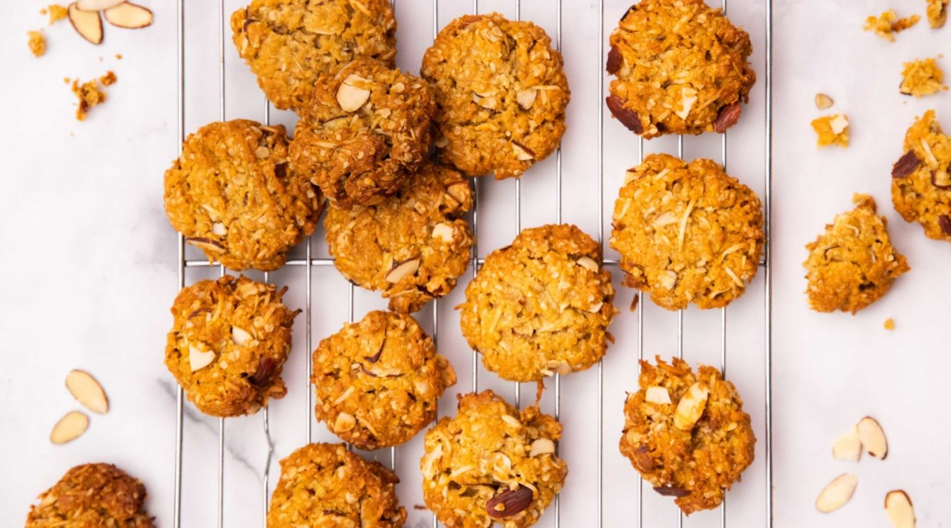 14 Anzac biscuits with sliced almonds on silver wire rack on white board, almond slices and broken biscuits around