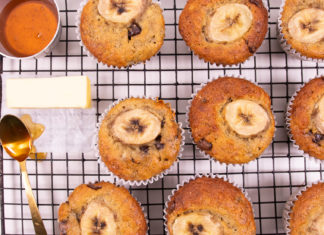 9 banana cupcakes on wire rack with a piece of butter, a spoon and a pot of brown liquid.