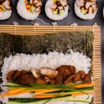 A nori sheet topped with rice and colourful chicken and vege fillings unrolled on bamboo mat. Four pieces of cut sushi on top, and three dishes of soy, wasabi and ginger on right.