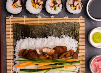 A nori sheet topped with rice and colourful chicken and vege fillings unrolled on bamboo mat. 4 rolled annd cut sushi on top, 3 dishes of soy, wasabi and ginger on right.