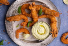 Deep fried crumbed prawns on a metal tray with a bot of pale green dipping sauce on blue background.