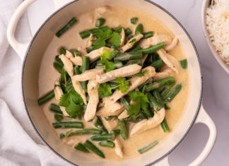 Creamy coloured soup with chicken pieces, green beans and herbs in a white double handled pan and a part view of white rice in a bowl on side.