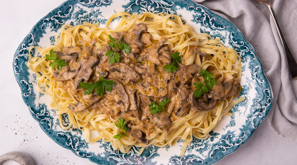 A platter of pasta topped with creamy mushroom sauce totted with green herbs on blue decorative platter.