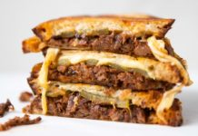 3 Beef and cheese toasties stack together on white background with a little beef spilling.