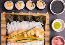 A black nori sheet on a bamboo mat with rice, cooked prawns and vege on top ready to roll. 4 rolled sushi on top and 3 dishes of soy sauce, wasabi and ginger on right side.