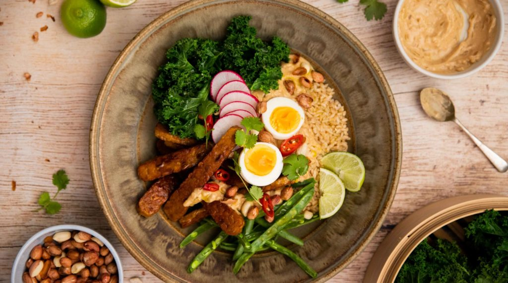 A brown bowl filled with colourful foods, brown sticks, boild egg halves, green veges and limes. Small bowls of peanuts, sauce and a spoon around it on wood background.