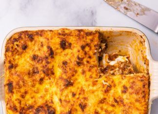 A top part of lasagne with a portion taken out and a knife on marble board.