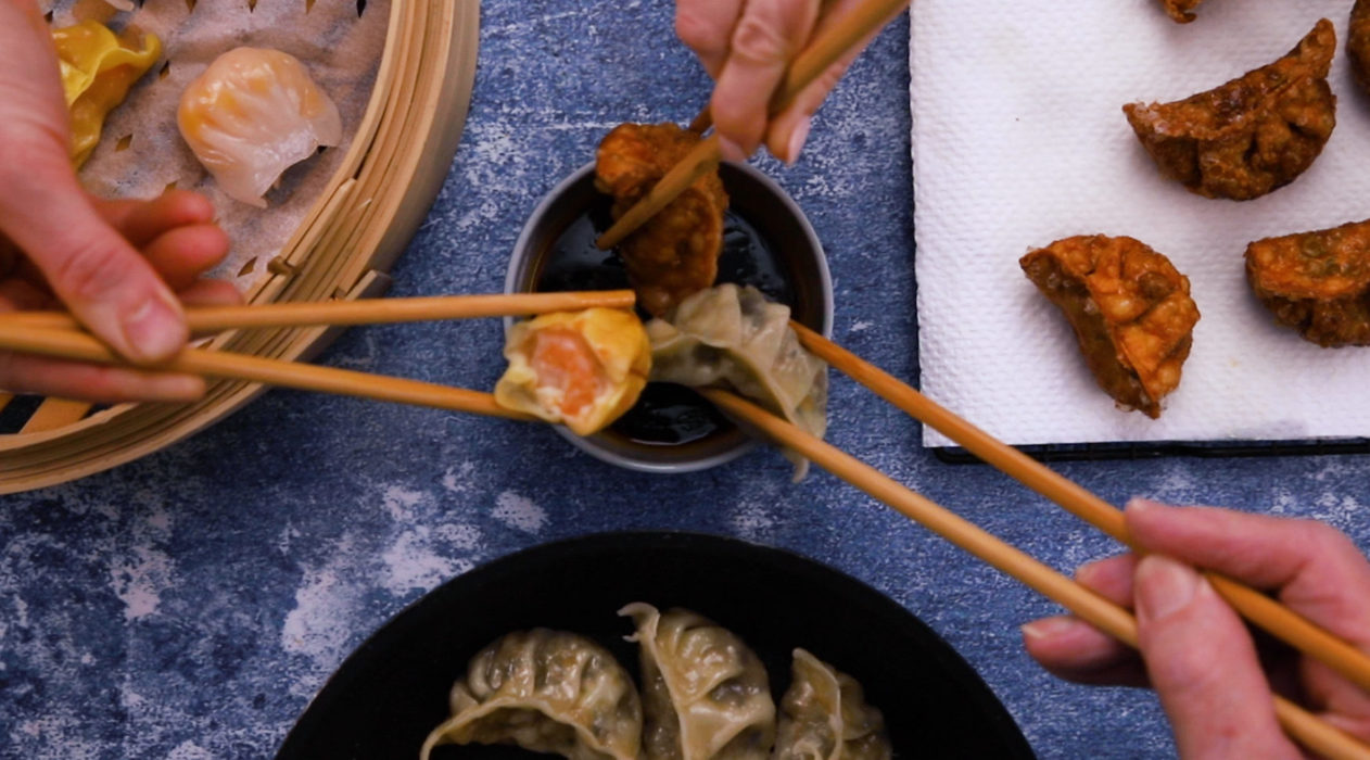 3 hands each dipping a dumplings cooked in 3 different ways using chopsticks, more dumplings shown around them.