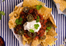 On a blue striped mat, a bowl of corn chips topped with red black chilli, a blob of white cream, pieces of green chilli and herb. Ingredients in corners outside of the bowl.