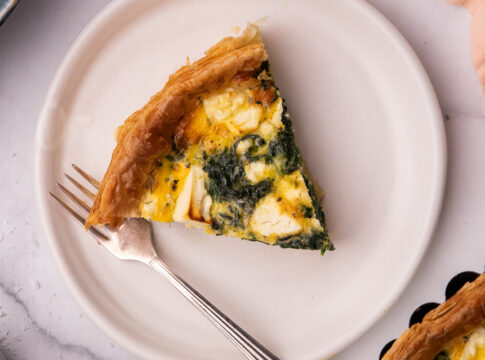 A slice of green and white quiche on a white round plate with a fork. A small part of the whole quiche shown on one corner with a pink cloth.