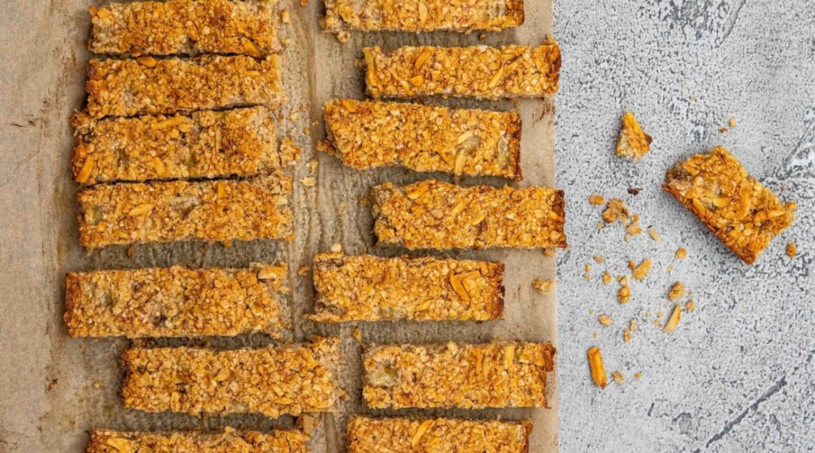 Baked oaty bars on baking paper on marble board