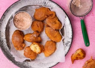 10 golden brown fried donut and a small pot of sugar on a metal plate on pink background with 2 more donut and a tea strainer at side.