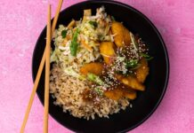 A round black bowl filled with brown rice, shredded vege salad and crumbed chicken with chopsticks on pink background