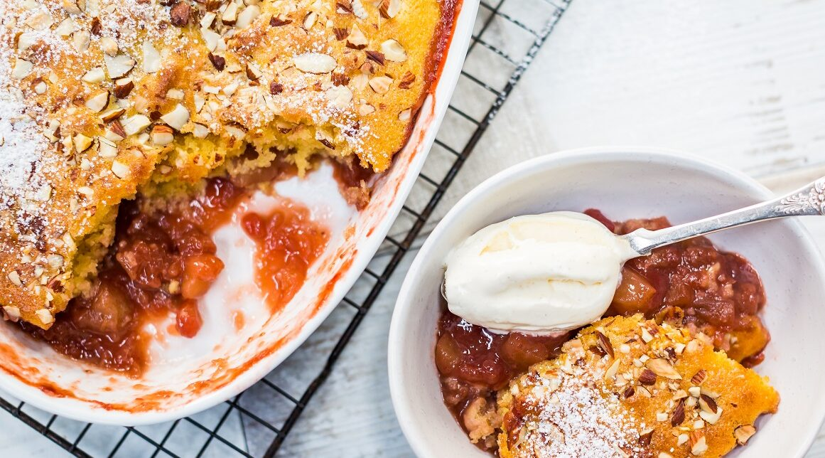 Brown and red baked pudding in an oval dish and a single helping in a bowl with a spoon full of white cream.