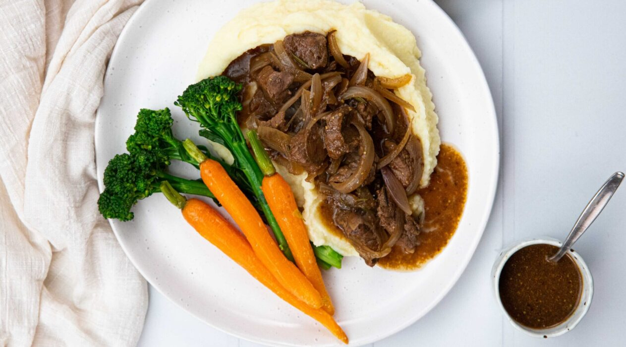 A plate of dark brown beef stew on potato mash with baby carrots and green vegetable on a white plate and a small pot of dark sauce.