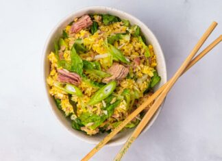 A bowl of yellow fried rice mixed with pink tuna meat, lettuce and spring onion slices and a pair of wooden chop sticks