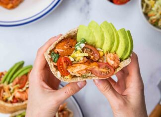 Hands folding a pita bread filled with tomato, salmon and avocado.
