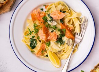 A pasta dish with salmon, greens and lemon on a blue rimmed plate with a fork on white board and cheesy toasts at sides.